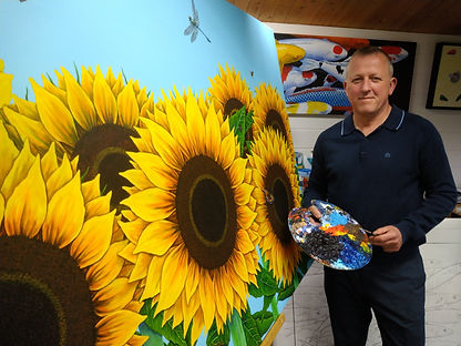 Keith in his Studio with the Sunflowers painting, 'From now on in it's strictly Blue Sky'