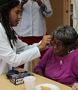 A medical professional helping a patient with her hearing aid