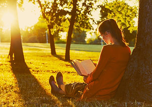 girl reading book at park in summer suns