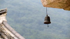 A hanging bell against a blue sky background
