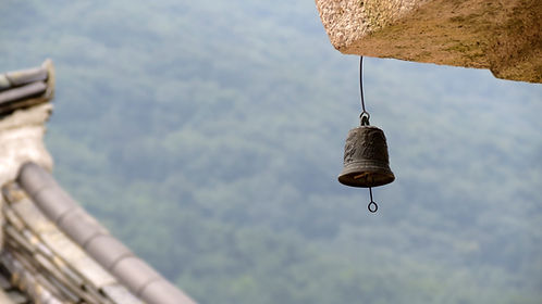 grey metal bell hanging from beam