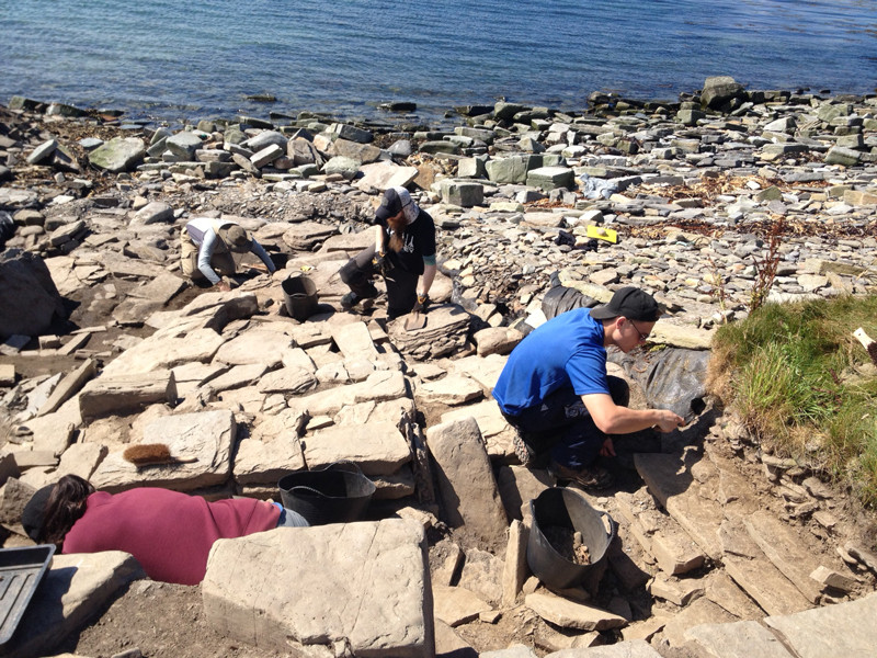 Cleaning the entrance passageway at the chambered tomb at Swandro, orkney