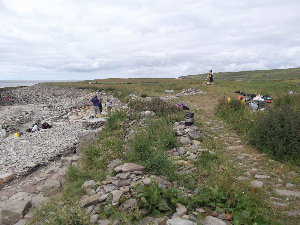 Looking north west across the site at Swandro, the surveyor is standing on top of the chambered tomb
