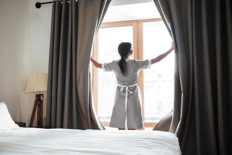 female-chambermaid-opening-window-curtai