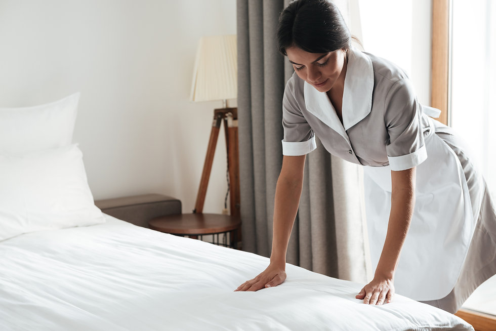 maid-setting-up-white-bed-sheet-in-hotel