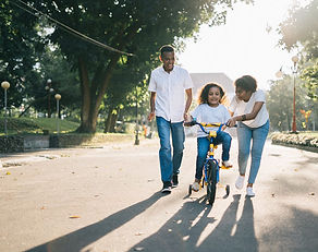 Adults teaching their child how to ride a bike