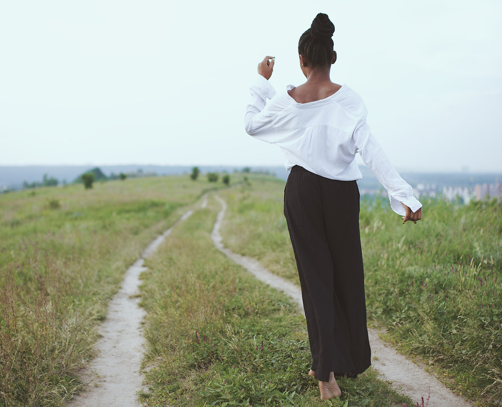 Black woman walking through valley in nature being fit and healthy getting vitamin D