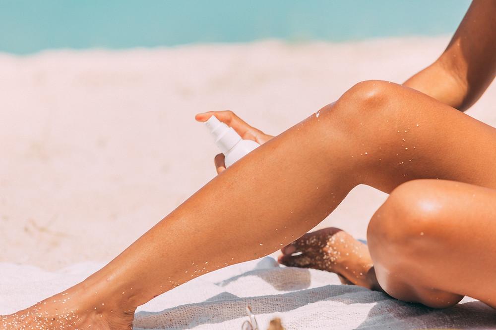 woman's legs, sunshine, beach, sunscreen, SPF, sun protection, applying lotion