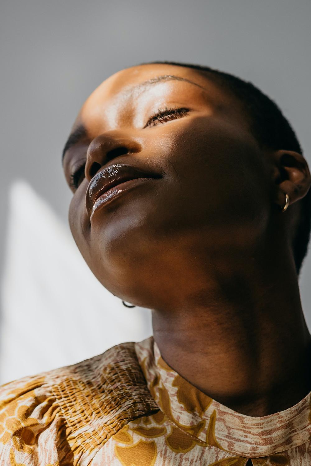 Black woman under sunlight in the shade, sunrays