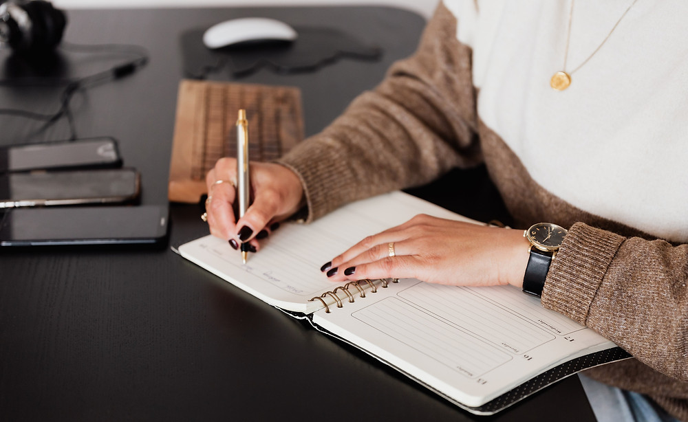 Woman journalling for mental health and to plan and be organised well-being wellness