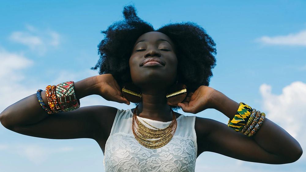 Black woman, afro hair, sky, SPF, sunscreen, dark skin, melanin