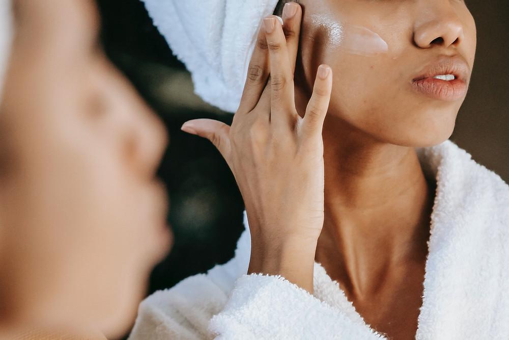 Black woman moisturising skin treatment selfcare