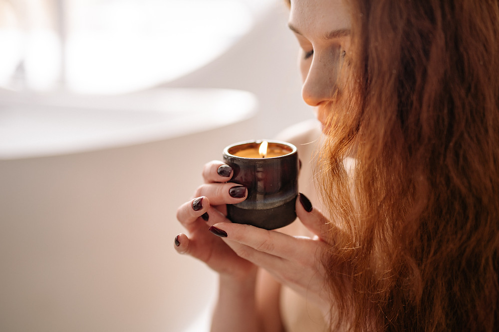 woman smelling a candle, aromatherapy, relaxing