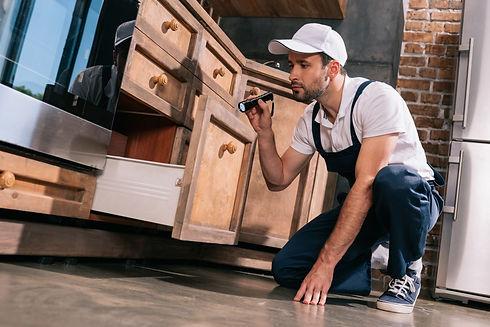 pest control worker examining kitchen wi