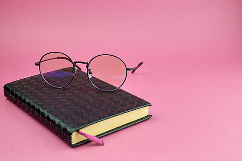 Round glasses and a notebook. Black leat