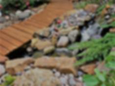 на фото альпийская горка с камнями и ручьем