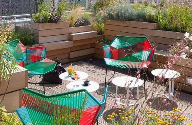 Пример озеленения крыш с деревянными горшками и высаженными растениями. Садовая мебельпрекрасн дополняет композицию из растений