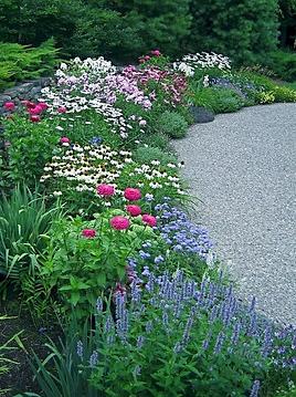 На фото Ландшафтный Дизайн красивой клумбы с растениями и цветами. Проект этой оригинальной и необычной клумбы предполагает ее устройство с использованием многоярусной структуры.  клумбы с цветущими растениями. Купить проект и устройство многоярусной клумбы по лучшей стоимости можно у ландшафтной компании Ваш Новый Сад.