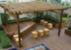 озеленение крыши  в Киве с монтажом перголы и деревянным настилом, на котором расположены стильные горшки и другие обьекты