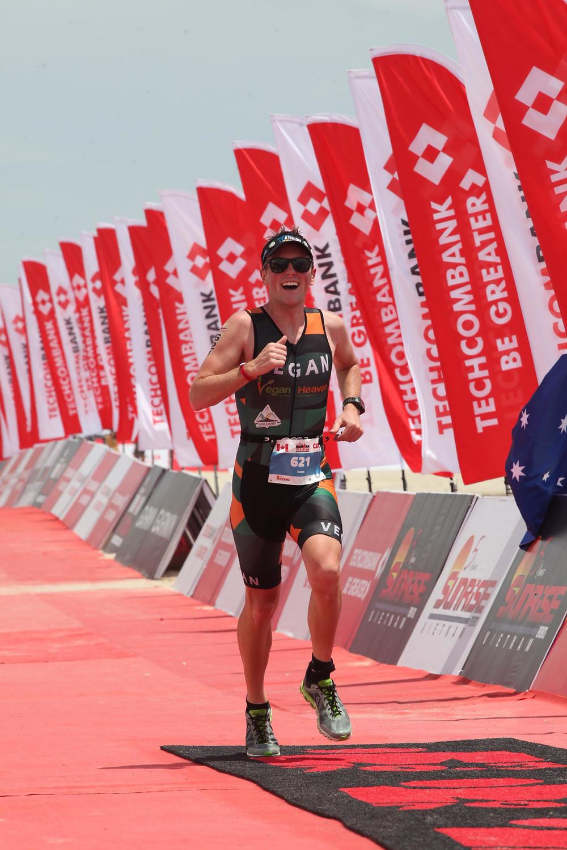 Jason Fonger vegan champion triathlete running to the finish line of Ironman 70.3 Vietnam 2019 Asia-Pacific Championships