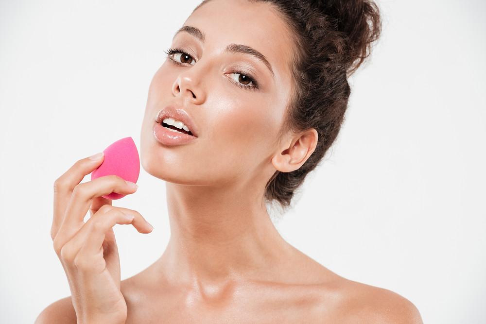 Woman applying makeup with a beauty sponge