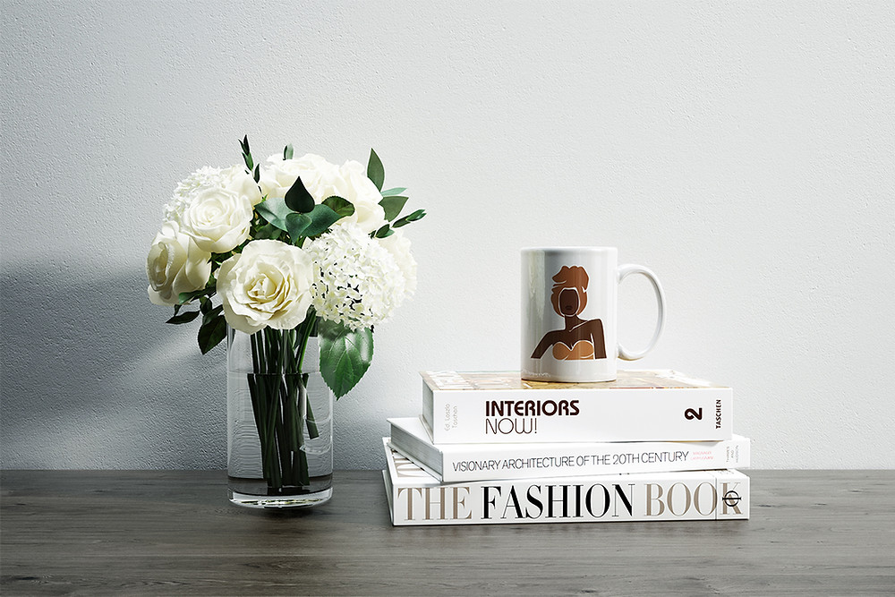 Coffee mug placed on a stack of books beside a beautiful glass vase of white flowers