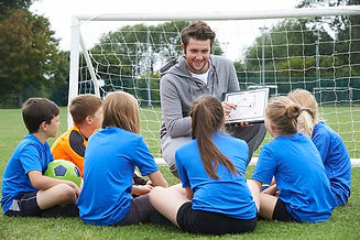 Coach-Giving-Team-Talk-To-Elementary-Sch