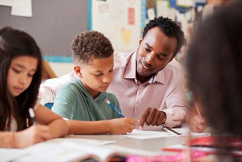 Male-teacher-working-with-elementary-sch