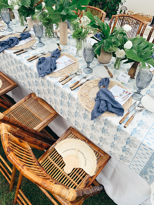 Beautiful bamboo chairs complimenting blue linens and rustic flatwares
