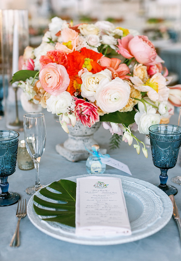Blue table setting with beautiful colorful floral centerpiece