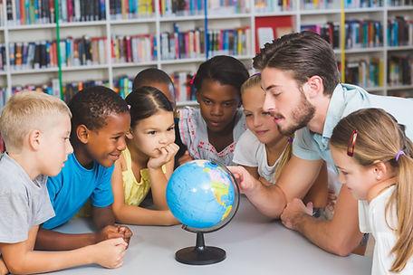students gathered around a globe