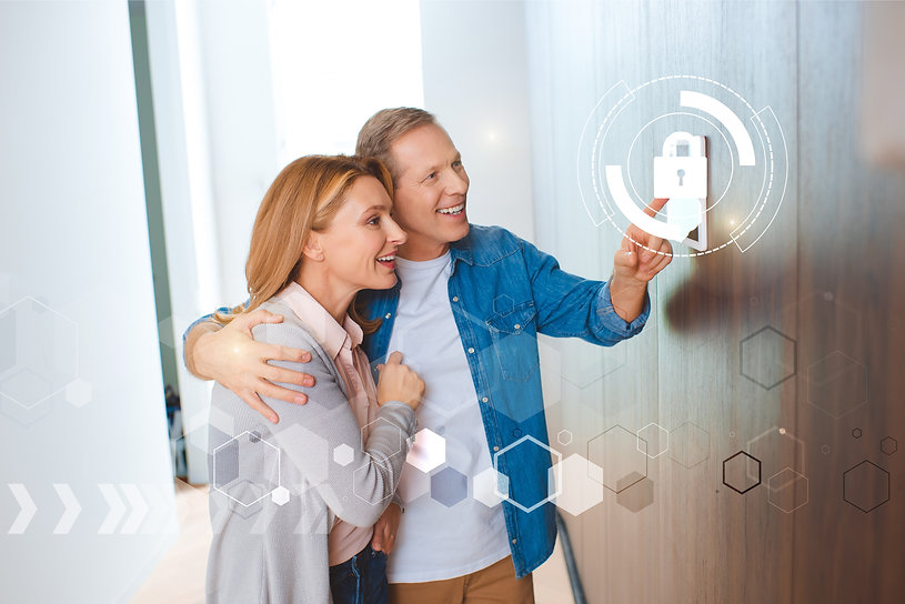 husband pointing at smart home security system control panel and hugging happy wife