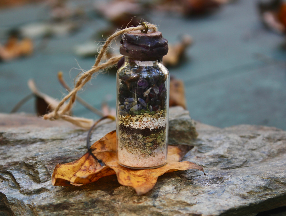 Small glass bottle filled with medicine herbs and precious stones, sitting on rock outside surrounded by autumn leaves