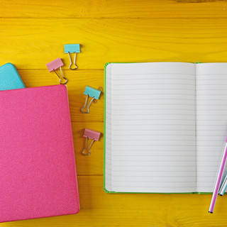 Colorful notebooks on wooden background.