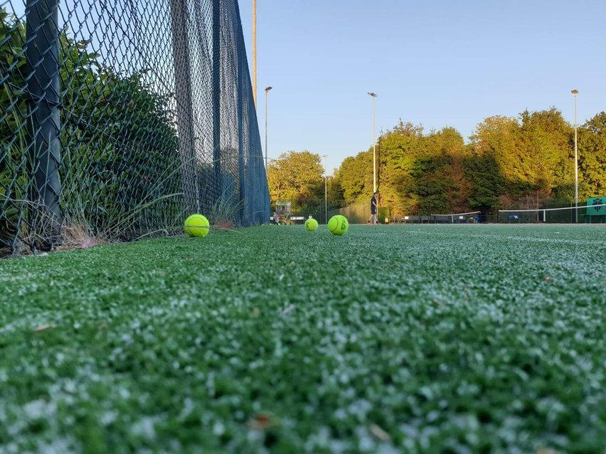 Tennisbaan met ballen op grond.jpg