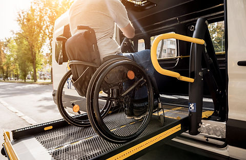 A man in a wheelchair on a lift of a veh