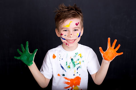 Happy cute boy colors his hands. Doing F