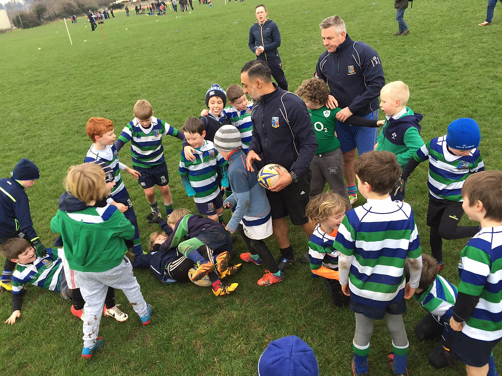 Under 8 Rugby team with coach sitting on the field