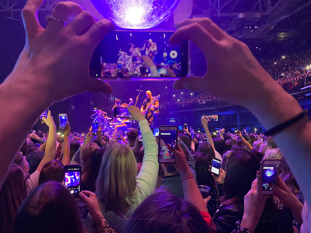 Crowd in a live concert with people taking photos on their smartphones