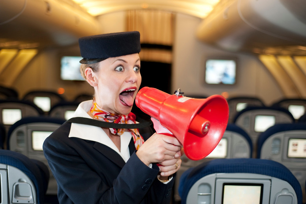 airline stewardess yelling into a red megaphone in a plane