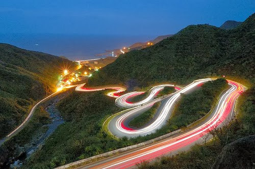 long winding road in the mountains leading to the ocean