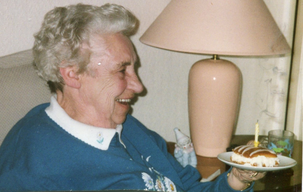 an elderly woman sitting on a couch, next to a side table and lamp, smiling and laughing