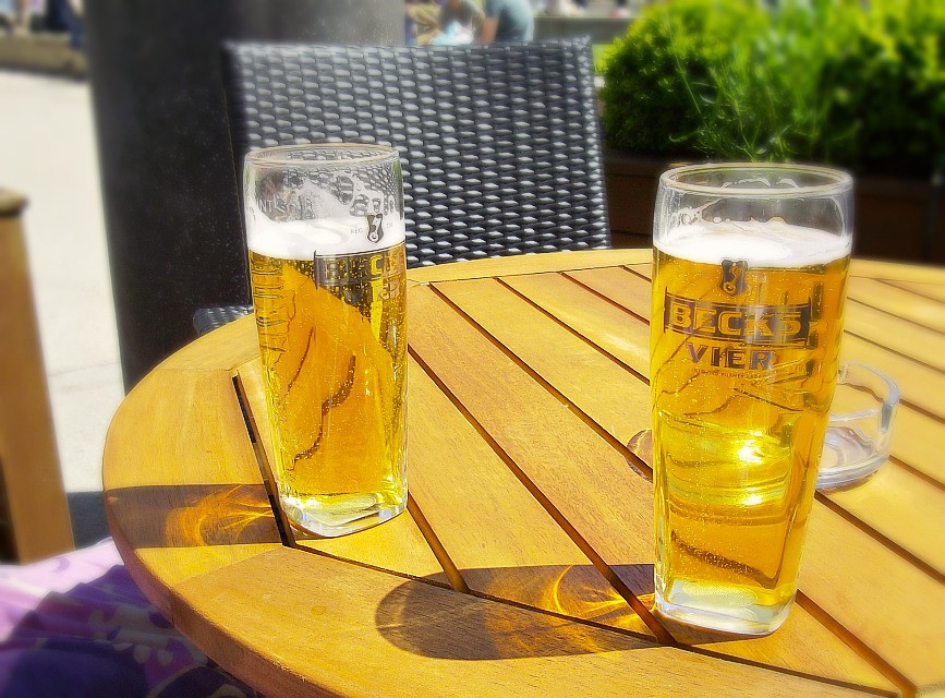 two full glasses of beer on a sunny patio table