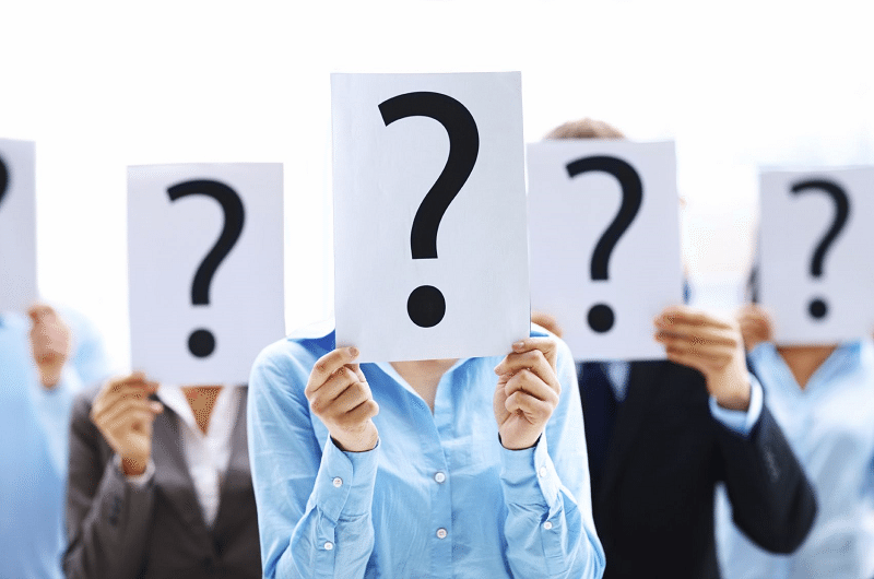 group of people holding up question marks over their faces