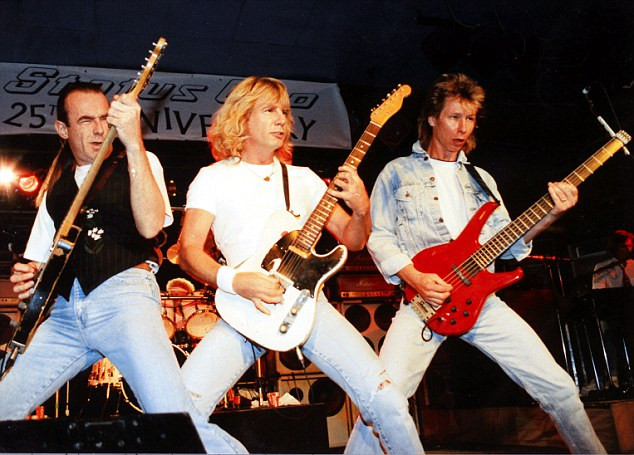 three men playing guitars in a rock band