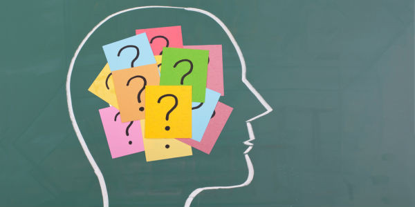 white chalk outline of the silhouette of a persons head; inside the outline there are multiple coloured sticky notes inside with question marks