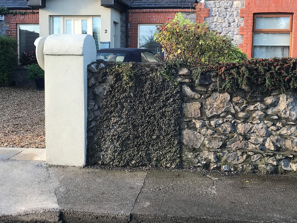 curbside with a stone wall covering the front of a house