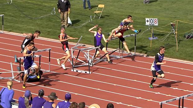 people running track jumping hurdles