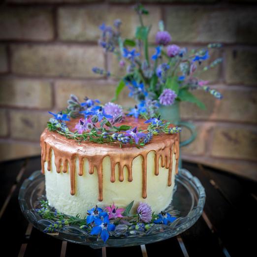 kates kakes gold drip cake with edible flowers