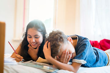 2 kids studying and laughing